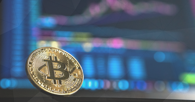 physical bitcoin with trading screens in the background