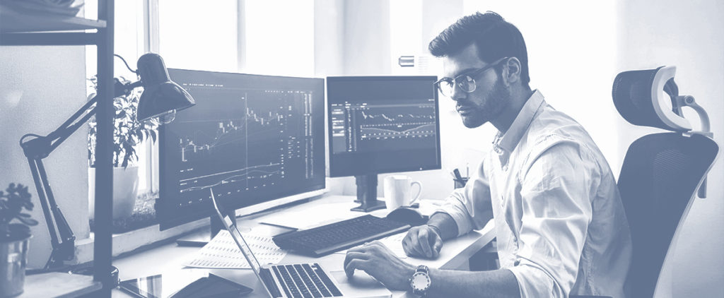 A man day trading in front of two computer screens